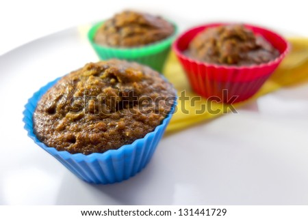 Breakfast muffins with dates, oats and pecans on a white plate with a yellow napkin in coloured silicone cases.