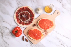 Breakfast of bread toasts with acorn-fed Iberian ham, tomato, garlic and olive oil (tumaca bread) on marble background