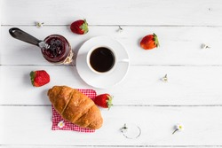Breakfast of coffee, jam, croissant and strawberry. Top view, flat lay