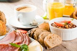 breakfast of coffee, juice, muesli, breads, ham and cheese