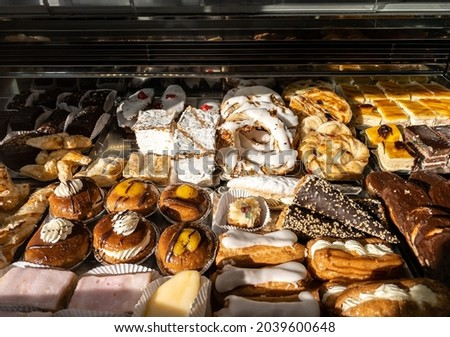 Breakfast of spanish biscuits, sweet pastries, puff pastry, powdered sugar and baked apples dessert. Typical sweets confections consumed in the window of a pastry shop at Spain.