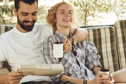breakfast of young beautiful couple on nature. man and woman reading news paper and laughing.