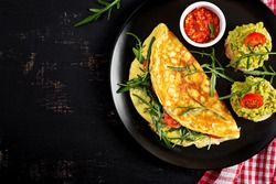 Breakfast. Omelette with tomatoes, cheese, green arugula and toasts with avocado cream on black plate. Frittata - italian omelet. Top view