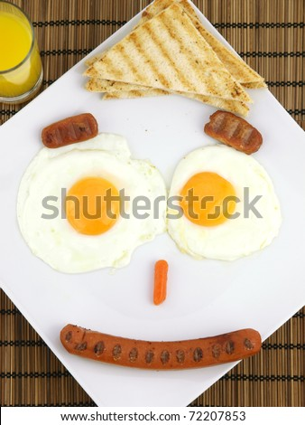 Breakfast on a plate of a funny face made from fried eggs, sausages and toast - stock photo