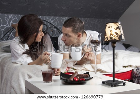 Breakfast on a table with couple lying in background at resort