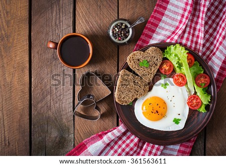 Breakfast on Valentine\'s Day - fried eggs and bread in the shape of a heart and fresh vegetables. Top view
