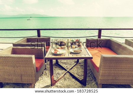 Breakfast outside at the hotel by the sea. Modern outdoor ocean view restaurant. Toned image