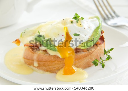 Breakfast. Poached egg with hollandaise sauce, bacon and avocado.