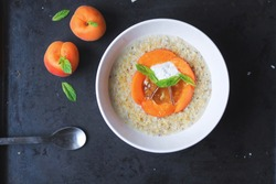 breakfast porridge with peaches nuts and ricotta cheese