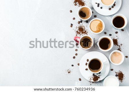 Breakfast relaxation time concept. Different coffee mugs and cups on a cozy kitchen table. Copy space, top view flat lay background