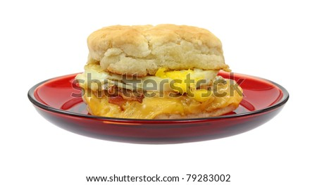 Breakfast sandwich biscuit with bacon egg and cheese on a red dish.
