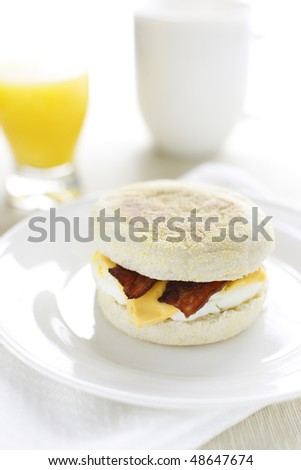 breakfast sandwich with egg,cheese and bacon in  english muffin bread.Orange juice and coffee cup in the background. Bright image with shallow depth of field.