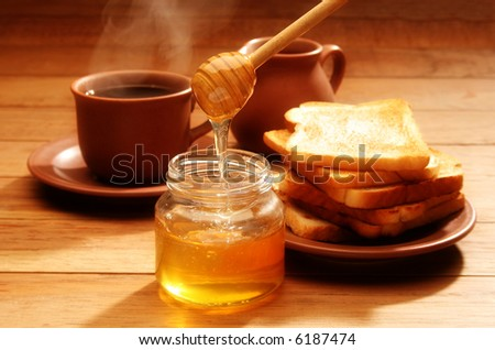 Breakfast scene. Honey pouring from glass jar