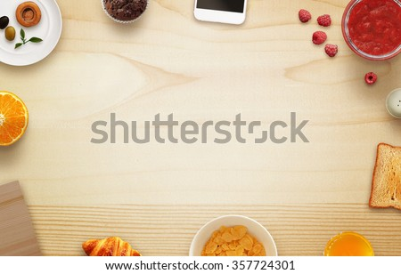 Photo of Breakfast scene with free space, tablecloth, fruits, toast, jar of jam, phone, cutting board on table. Top view.