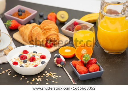 Breakfast Served in the morning with Coffee, Butter croissant and corn flakes Whole grains and raisins with milk in cups and Strawberry, Raspberry, Kiwi, Fresh Orange Juice on the breakfast table. Photo stock ©