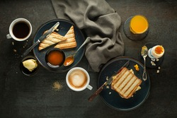 Breakfast served with coffee, juice, toast sandwich, boiled egg, and jam with butter. Delicious healthy breakfast.