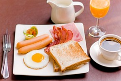 Breakfast set, bread, ham, bacon, fried egg, orange juice and coffee