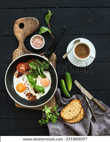 Breakfast set. Pan of fried eggs, bacon, tomatoes with bread, mangold and cucumbers, coffee on rustic wooden serving board over dark table surface, top view