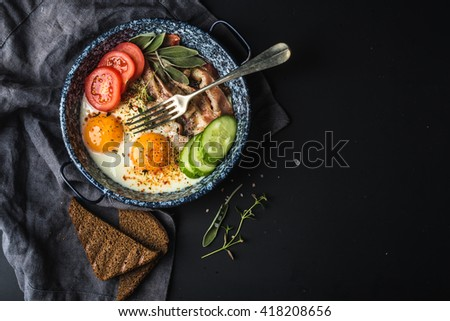 Breakfast set. Pan of fried eggs with bacon, fresh tomato, cucumber, sage and bread on dark serving board over black background, top view, copy space #418208656