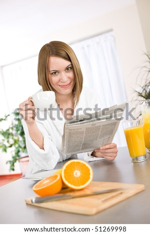 Breakfast - Smiling woman reading newspaper in kitchen, with coffee and fresh orange juice