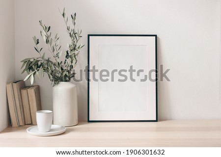 Breakfast still life. Cup of coffee, books and empty picture frame mockup on wooden desk, table. Vase with olive branches. Elegant working space, home office concept. Scandinavian interior design.