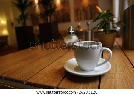 Breakfast table near to the window with a cup of coffe