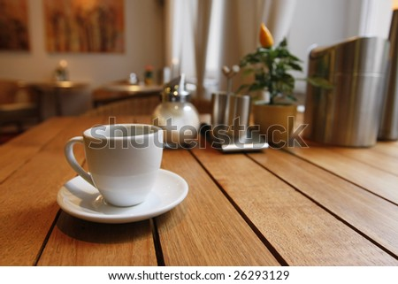 Breakfast table near to the window with a cup of coffee