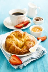 Breakfast table with croissant, marmalade and coffee