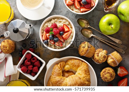 Breakfast table with oatmeal porridge, croissants, fresh fruit and muffins overhead shot #571739935