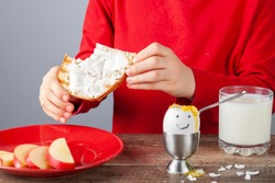 Breakfast table with simple balanced nutritious ingredients. A soft boiled egg with face painted on, a slice of toasted bread with cream cheese spread, apple, a glass of milk with a girl eating.
