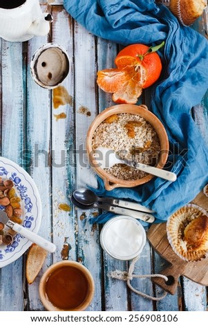 Breakfast table with whole oat flakes, nuts, honey and natural yogurt on a vintage blue wooden table. Concept image for healthy or vegetarian cooking.Natural fruit of garden Rustic style