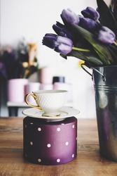 Breakfast time with tea and lilac fresh tulips. Flowers shop. Breakfast mood. Spring. White beautiful cup