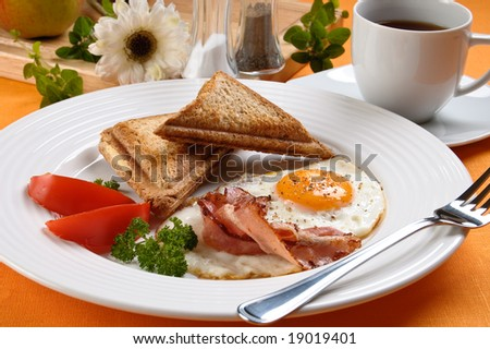 Breakfast - toasts, egg, bacon and vegetables