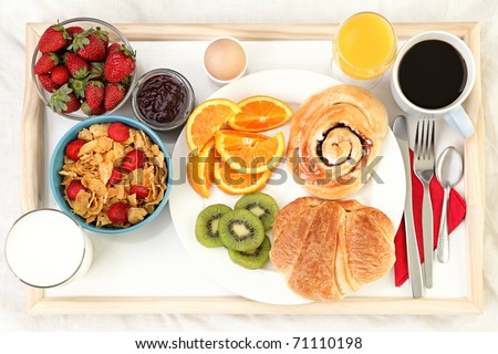 Breakfast tray in bed with coffee, bread, cereals, fruit etc.
