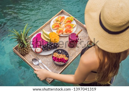 Breakfast tray in swimming pool, floating breakfast in luxury hotel. Girl relaxing in the pool drinking smoothies and eating fruit plate, smoothie bowl by the hotel pool. Exotic summer diet. Tropical