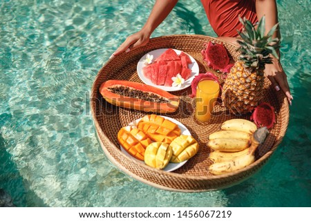 Breakfast tray in swimming pool, floating breakfast in luxury hotel smoothies and fruit plate, smoothie bowl by the hotel pool. Exotic summer diet. Tropical beach lifestyle. Bali