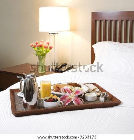stock photo : Breakfast tray laying on white bed in upscale hotel.