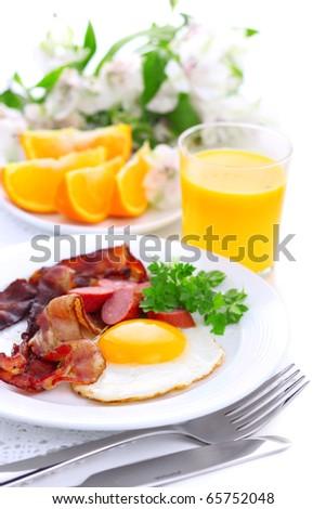Breakfast with bacon, fried egg and orange juice on white isolated background