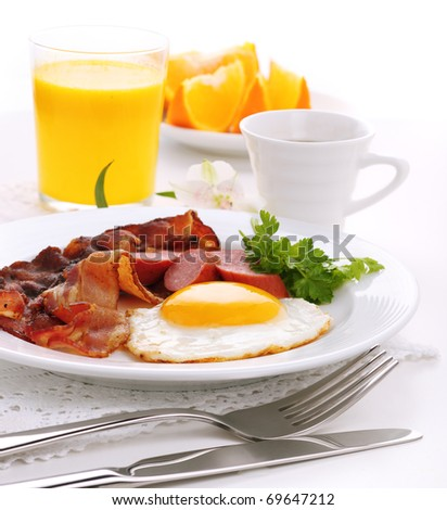 Breakfast with bacon fried egg and orange juice on white isolated background