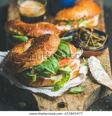 Shutterstock Breakfast with bagels with salmon, avocado, cream-cheese, basil, espresso coffee, capers on rustic wooden board over dark background, selective focus, square crop. Healthy or diet food concept