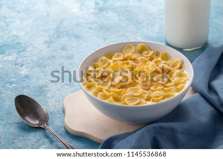 Breakfast with cereal. Flakes with milk. A white plate of cereal with milk on a blue table. Perfect for breakfast. Free space for text. #1145536868