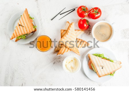 Breakfast with club sandwiches with fresh tomatoes, lettuce and cucumbers salmon (trout), coffee and freshly squeezed juice, on white stone concrete table top view copy space