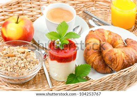 Breakfast with coffee, croissants, orange juice and fresh strawberry yogurt