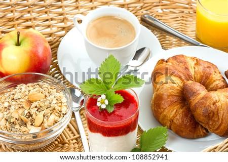 breakfast with coffee, croissants, orange juice and fresh strawberry yogurt