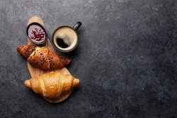 Breakfast with coffee, jam and croissant. Top view on stone table with copy space. Flat lay