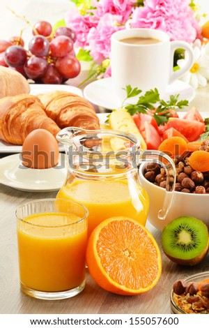 Breakfast with coffee orange juice croissant egg vegetables and fruits