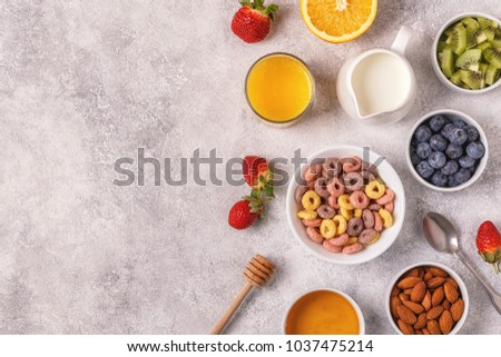Breakfast with colorful cereal rings, fruit, milk, juice. Top view. #1037475214