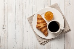 Breakfast with croissant, coffee and orange jam