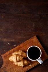 Breakfast with croissants and black coffee on wooden cutting board over rustic background, close-up, selective focus