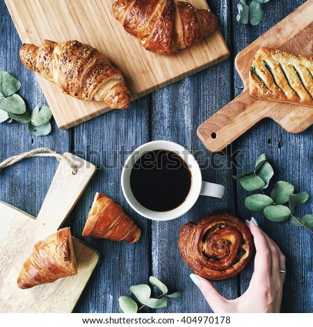 Breakfast with croissants, leaves, cutting board and black coffee composition with girl hand on wooden retro background. Flat lay, top view